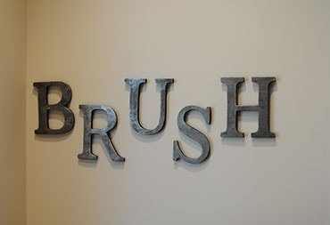 A sign on our wall that says Brush