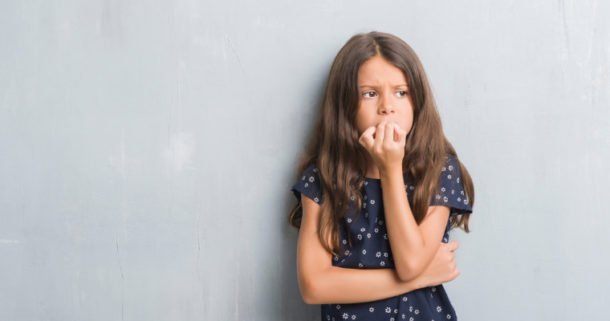 Young girl biting her nails, which can damage her smile.