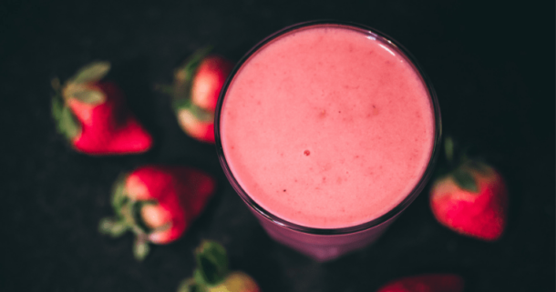 Top of strawberry smoothie snack with strawberries around
