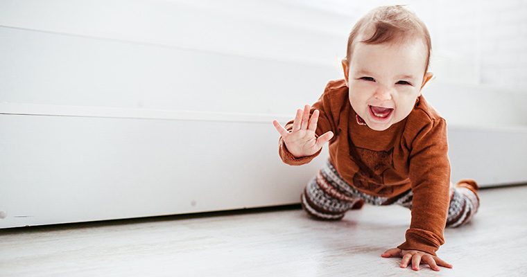 teething baby crawling on floor